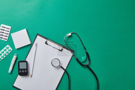 Photo for Top view of blood lancet, sticky notes, blister packs and stethoscope near glucometer and pencil on folder on green background - Royalty Free Image