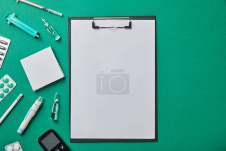 Photo for Top view of various medical supplies near folder and on green surface - Royalty Free Image