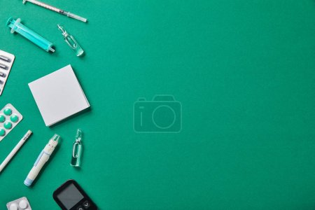 Photo for Blister packs, ampules, blood lancet, glucometer, syringes, sticky notes and pencil on green background - Royalty Free Image