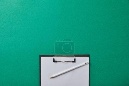 vue du haut du crayon sur dossier avec papier blanc isolé sur vert