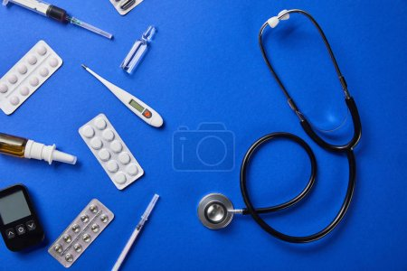 Photo for Top view of stethoscope near various medical supplies on blue background - Royalty Free Image