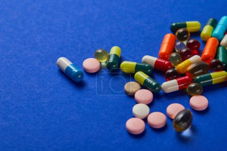 Photo for Various colorful scattered medical pills on blue background - Royalty Free Image