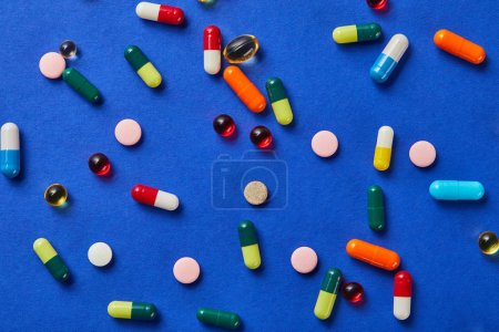 Photo for Top view of different medical pills on blue background - Royalty Free Image
