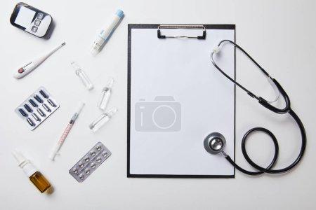 Photo pour Vue du dessus de diverses fournitures médicales près du dossier avec papier blanc et stéthoscope sur blanc - image libre de droit