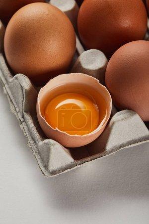 cáscara de huevo rota con yema amarilla cerca de los huevos en caja de cartón