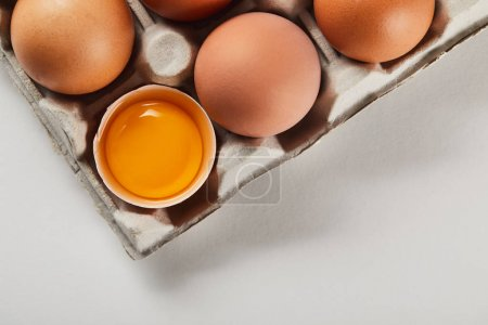 Photo for Top view of broken eggshell with yellow yolk near eggs in carton box - Royalty Free Image