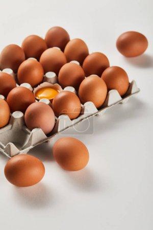 Photo pour Coquille d'œuf cassée avec le jaune jaune près des oeufs dans la boîte de carton - image libre de droit