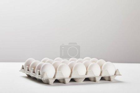 Photo pour Oeufs de poulet dans la boîte de carton sur la surface blanche - image libre de droit