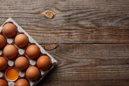 vista superior de huevos de pollo en caja de cartón sobre mesa de madera