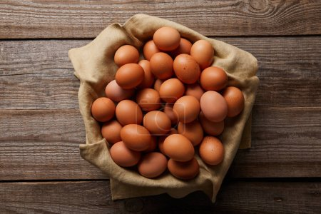 top view of chicken eggs at cloth on wooden table