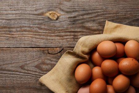 vista superior de huevos de pollo en tela sobre mesa de madera