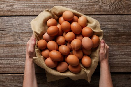 Photo for Top view of man holding chicken eggs in cloth over wooden table - Royalty Free Image