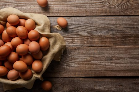 Photo for Top view of chicken eggs at cloth on wooden table - Royalty Free Image