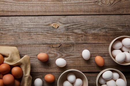 Foto de Vista superior de los huevos de pollo en cuencos sobre mesa de madera con tela - Imagen libre de derechos