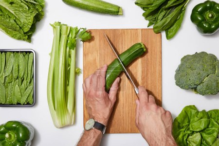 Photo for Top view of man cutting green vegetables on wooden chopping board white background - Royalty Free Image