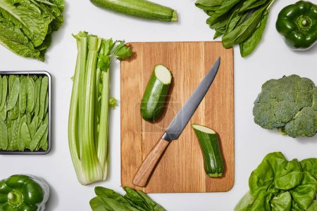Foto de Top view of green vegetables and chopping board with knife on white background - Imagen libre de derechos
