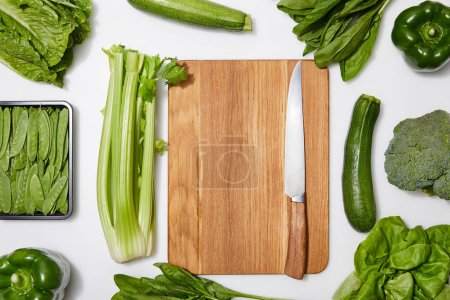 Photo for Top view of green vegetables around wooden chopping board with knife on white background - Royalty Free Image