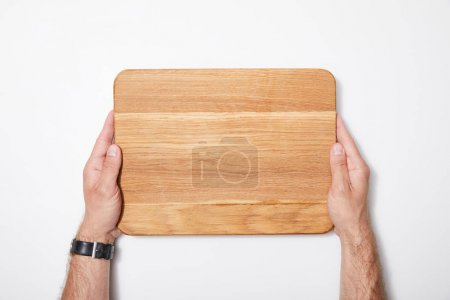 Photo for Top view of man holding wooden chopping board on white background - Royalty Free Image