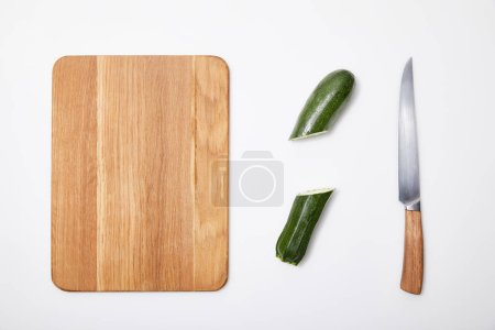 Photo for Top view of green cut zucchini near wooden chopping board and knife on white background - Royalty Free Image