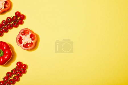 Photo for Top view of red cherry tomatoes and paprika on yellow background - Royalty Free Image