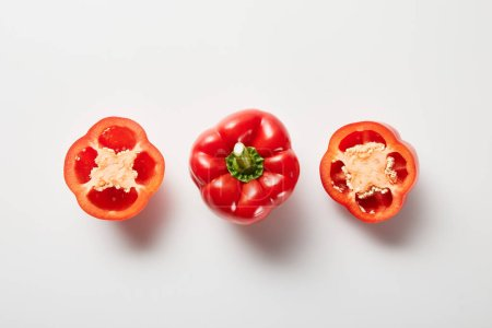 Photo for Top view of red organic cut and whole bell peppers on white background - Royalty Free Image