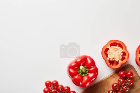 Photo for Top view of red organic vegetables and wooden chopping board on white background - Royalty Free Image