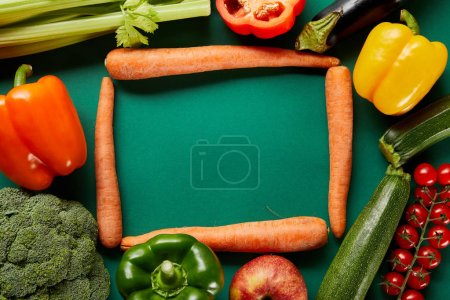 Photo for Frame of green fresh vegetables and carrots on green background - Royalty Free Image