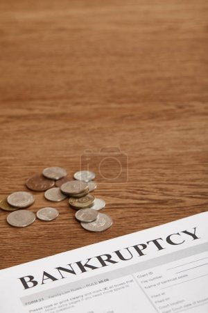 Photo for Bankruptcy form and coins on brown wooden table - Royalty Free Image