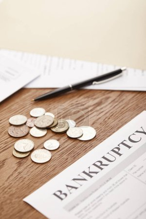 Photo for Selective focus of bankruptcy form, pen, coins and documents on brown wooden table - Royalty Free Image