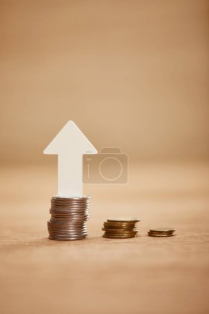 Photo for Increasing chart made of coins with white arrow upwards, financial growth concept - Royalty Free Image