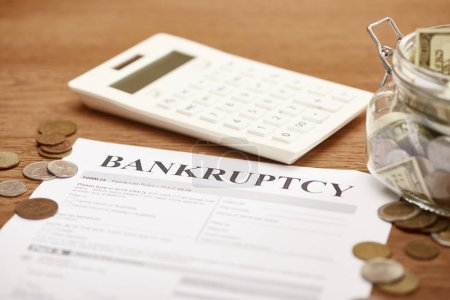 selective focus of bankruptcy form, coins, calculator and glass jar with dollar banknotes on wooden table