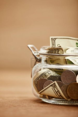 Photo for Close up view of glass jar with dollar banknotes and coins - Royalty Free Image