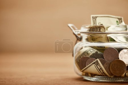 Photo for Close up view of glass jar with dollar banknotes and metal coins - Royalty Free Image