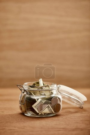 Photo for Opened glass jar with dollar banknotes and coins on wooden table - Royalty Free Image