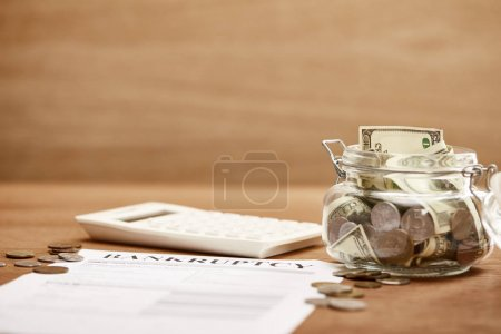 Photo for Selective focus of bankruptcy form, coins, calculator and glass jar with dollar banknotes - Royalty Free Image