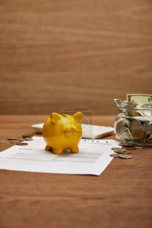 Photo for Selective focus of bankruptcy form, coins, yellow piggy bank, calculator and glass jar with dollar banknotes on wooden table - Royalty Free Image