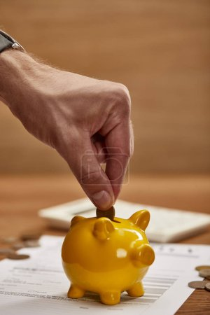 Photo for Partial view of man putting coin in yellow piggy bank - Royalty Free Image