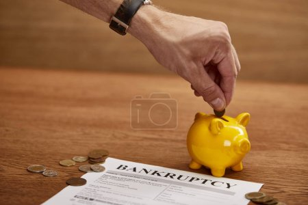 Photo for Cropped view of man putting coin in yellow piggy bank near bankruptcy form - Royalty Free Image
