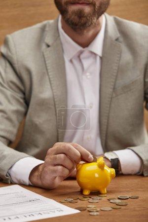 abgeschnittene Ansicht des Geschäftsmannes in Klage, der Münze in gelbes Sparschwein nahe Konkursformular legt