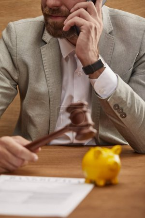 Photo for Cropped view of businessman in suit talking on smartphone while holding wooden gavel near yellow piggy bank - Royalty Free Image