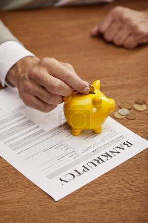 Photo for Cropped view of man putting coin in yellow piggy bank on bankruptcy form - Royalty Free Image