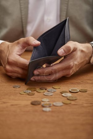 Photo for Cropped view of man showing empty wallet near coins on wooden table - Royalty Free Image