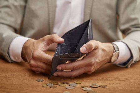 Photo for Partial view of man showing empty wallet near coins on wooden table - Royalty Free Image