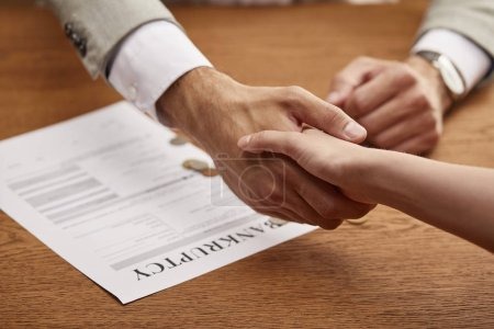 Photo for Partial view of man and woman shaking hands near bankruptcy form - Royalty Free Image