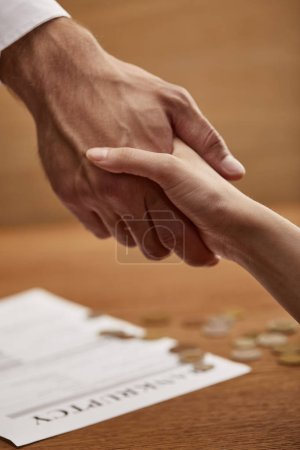 Photo for Selective focus of man and woman shaking hands near bankruptcy form - Royalty Free Image