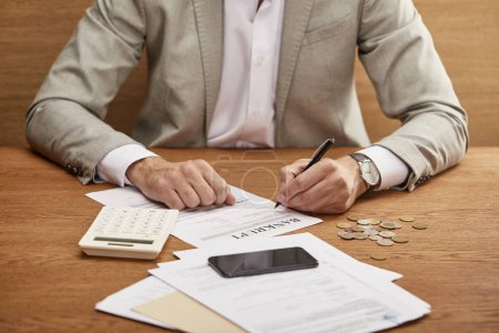 Photo for Cropped view of businessman in suit filling in bankruptcy form at wooden table - Royalty Free Image