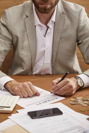 Photo pour Vue recadrée de l'homme d'affaires barbu dans le remplissage de costume dans la forme de faillite à la table en bois - image libre de droit