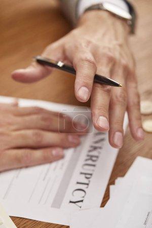 Photo pour Vue recadrée de stylo de fixation d'homme d'affaires au-dessus de la forme de faillite à la table en bois - image libre de droit