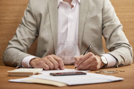 Photo for Partial view of businessman in suit filling in bankruptcy form at wooden table - Royalty Free Image