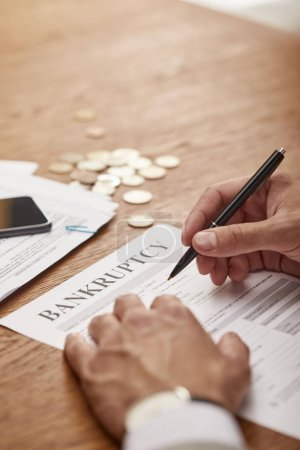 Photo for Cropped view of businessman in suit  filling in bankruptcy form at wooden table with coins - Royalty Free Image